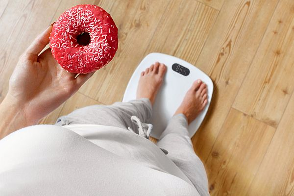 48712095 - diet. woman measuring body weight on weighing scale holding donut. sweets are unhealthy junk food. dieting, healthy eating, lifestyle. weight loss. obesity. top view